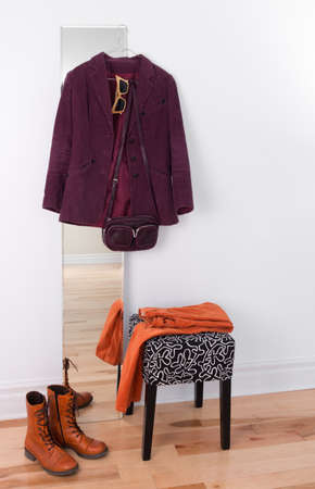 Purple jacket hanging on a mirror. Orange boots and pants, room reflection. Stock Photo - 17677389