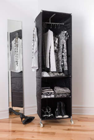 Mobile clothes organizer with black and white clothing and shoes. photo