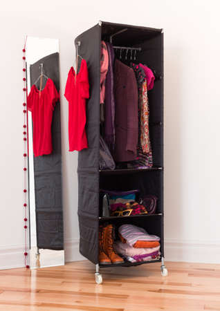 Mobile clothes organizer with red and purple clothing and accessories. photo