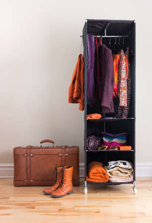 closet rod: Mobile wardrobe with orange and purple clothing, and leather suitcase.