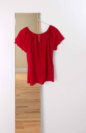 Red blouse hanging on a mirror. Room reflection. photo