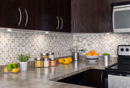 kitchen cabinet: Modern kitchen with cozy lighting, and food ingredients on the counter top