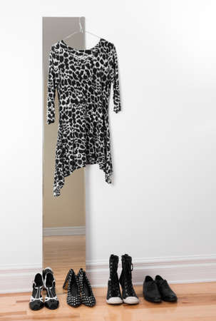 Row of black and white shoes, and stylish dress hanging on a mirror Stock Photo - 17677399