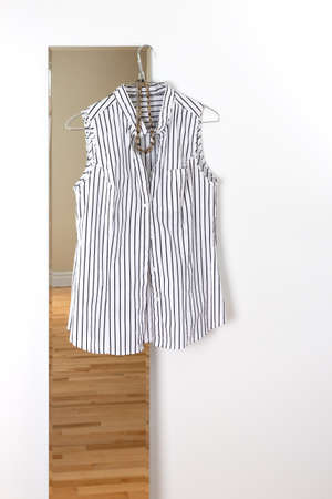 striped vest: White striped blouse hanging on a mirror  Room reflection