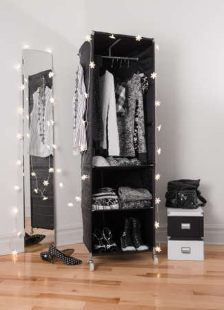 Lights decorating a mirror and a clothes organizer with black and white clothing  photo