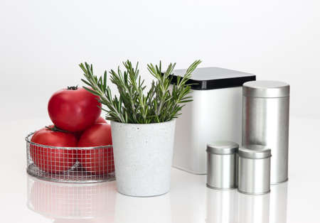Food storage containers, tomatoes and rosemary on white background  photo