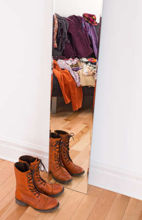Leather boots and heap of clothing reflecting in the mirror  photo