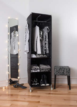 woman closet: Mirror and mobile wardrobe with black and white clothing and shoes  Stock Photo