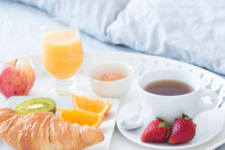 Close-up of tray with tasty breakfast on a bed