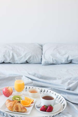 breakfast food: Tray with healthy breakfast on a bed with gray bed linen  Copy space  Stock Photo