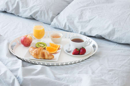 hotel bedroom: Tray with tasty breakfast on a bed with gray bed linen