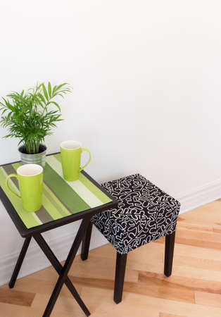 little table: Little table with bright cups and green plant  Stock Photo