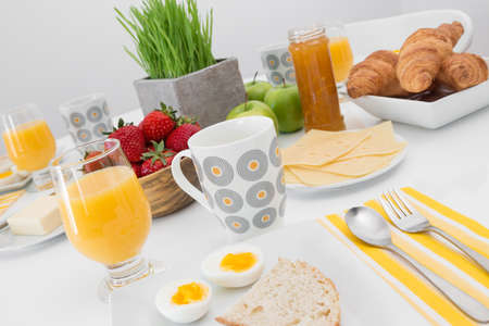 Tasty and healthy breakfast  Juice, eggs, fruits, comfiture, croissants  photo