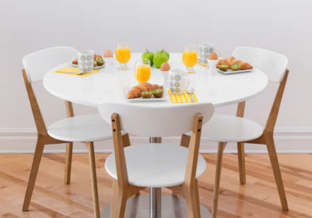 living room furniture: White round table with healthy breakfast for three