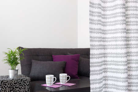 futon: Sofa with bright cushions, and tea served in a living room  Stock Photo