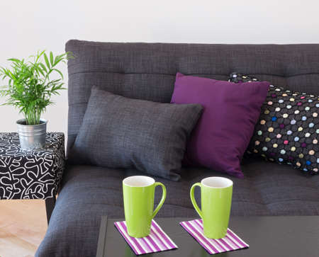 futon: Sofa decorated with bright cushions, green plant and big cups on a table