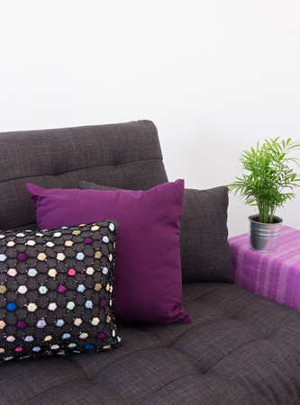 futon: Sofa decorated with colorful cushions, and green plant on side table  Stock Photo