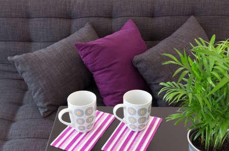 소파: 쿠션, 테이블 및 녹색 식물에 두 컵으로 장식 된 소파
