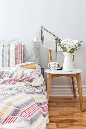 Lichte en frisse slaapkamer versierd met een boeket bloemen