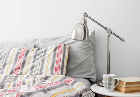 bedroom wall: Lamp and books on a side table near bed with colorful bed linen