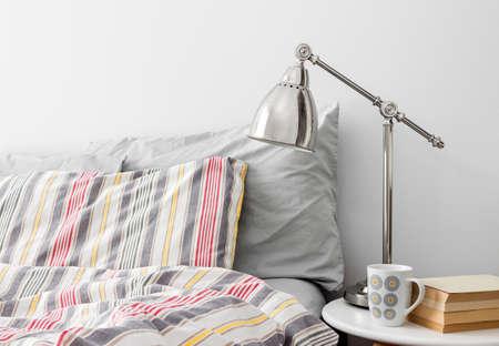 Lampa i książki na stoliku obok łóżka z kolorową pościelą