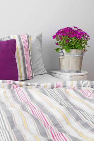 Modern bedroom decorated with purple flowers and cushions  Stock Photo