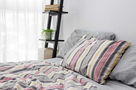 bedlinen: Lamp, books and green plant on a shelf decorating a modern bedroom