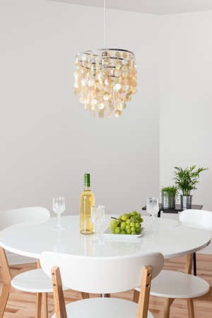 dining table and chairs: Room with decorative chandelier, white round table and plants