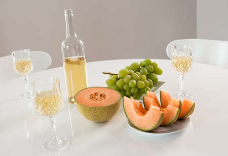 White wine with melon and grapes on a round table  photo