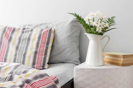 침대 신선한 디자인 가까운 쪽 테이블에 흰색 꽃과 책 스톡 콘텐츠