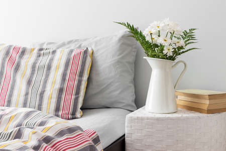 White flowers and books on a side table near a bed  Fresh design