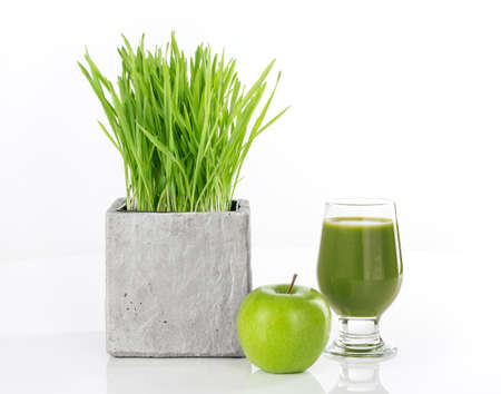 Wheatgrass, apple and a glass of fresh green juice, on white background  Stock fotó