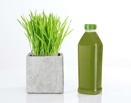 wheat grass: Wheatgrass and a bottle of fresh green juice, on white background  Stock Photo