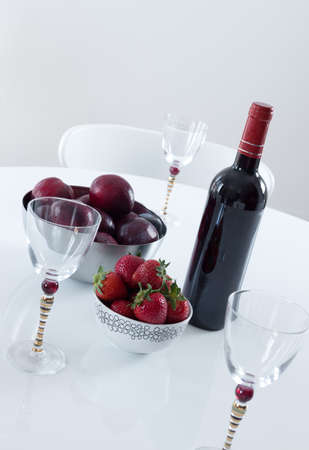 Red wine, plums and strawberries on a white table  photo