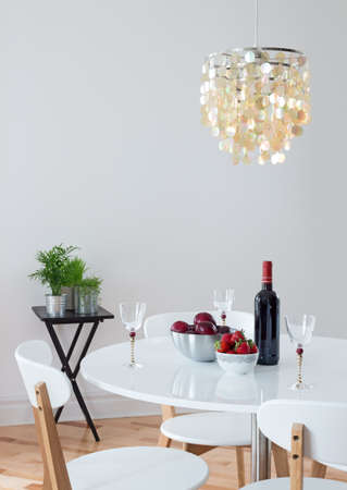 dining room: Dining room decorated with beautiful chandelier  Red wine and fruits on a table