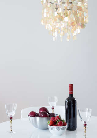 Red wine and fruits on a table, in a room decorated with beautiful chandelier  photo