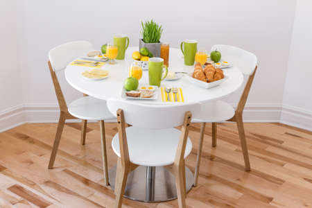 coffee table: Elegant round table with tasty breakfast for three
