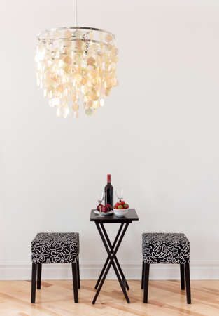 Table for two with bottle of red wine, in a room decorated with beautiful chandelier