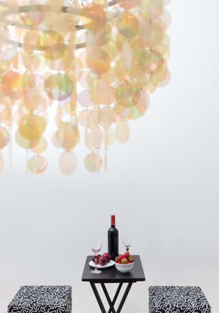 Bottle of red wine on a table, in a room decorated with beautiful chandelier  Focus on the table  Stock Photo - 20415510