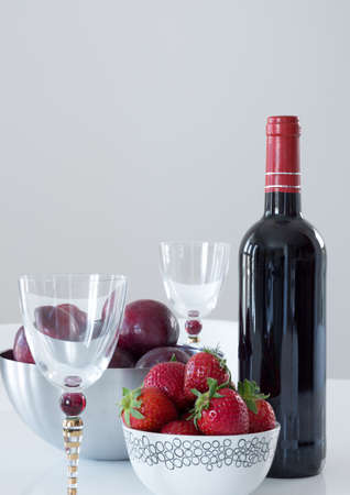 Red wine, elegant glasses, plums and strawberries on a table  photo