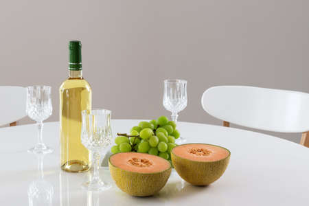 Round table with white wine, melon and green grapes  photo