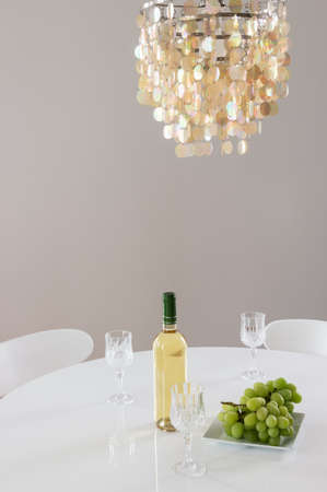 lamp: Decorative chandelier and bottle of white wine with grapes on the table