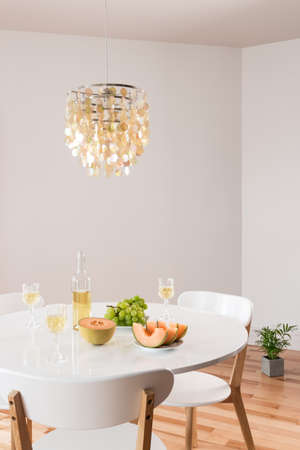 White wine and fruits on a table  Room decorated with beautiful chandelier  photo