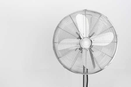 Modern metal electric fan on gray background.