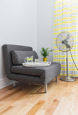 seating furniture: Armchair and electric fan in a contemporary living room. Stock Photo