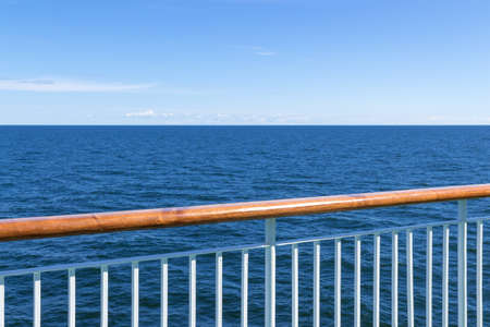 Passenger ship railing with sea and blue sky in the background  Stok Fotoğraf