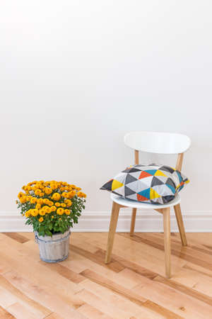 Bright cushion on a chair, and orange chrysanthemums decorating a room. Stockfoto