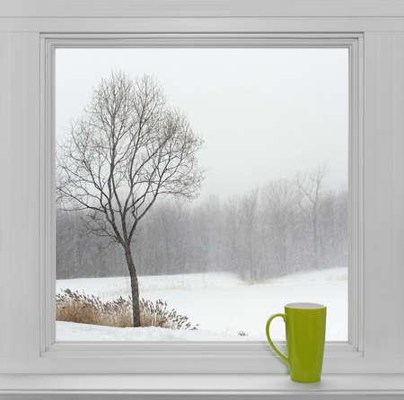 Xícara de chá verde em um peitoril da janela, com a paisagem de inverno vista através da janela