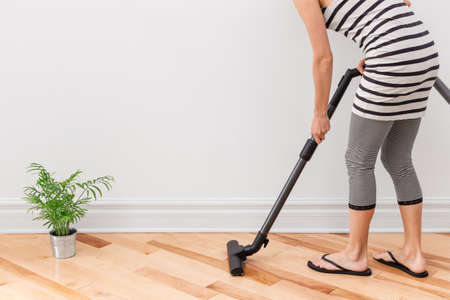 Housework  Young woman vacuum cleaning the apartment