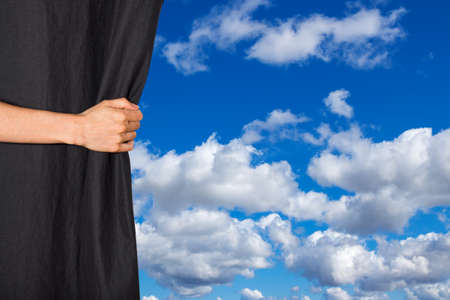 Hand opening black curtain with blue sky and clouds behind it.
